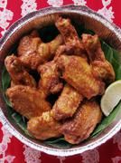 Chicken wings with wedge of lime in aluminium dish Stock Photos