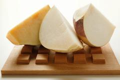 Three chunks of turnip on wooden board Stock Photos