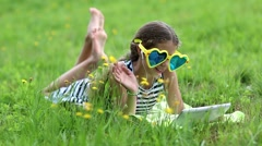 Girl in big sunglasses in the shape of hearts with tablet pc lies on green grass Stock Footage