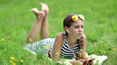 Attractive girl in sunglasses with red smartphone lies on the grass Stock Footage