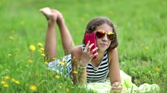 Beautiful girl in sunglasses with red smartphone lies on the grass Stock Footage