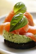 Pumpernickel rounds with salmon and basil Stock Photos