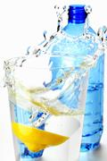 Lemon falling into glass of mineral water Stock Photos