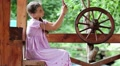 Girl with smartphone sits near wooden wheel HD Footage