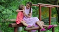 Two girls sits on a wooden bench and embrace Footage