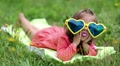 Funny little girl in big sunglasses in the shape of hearts lies on the grass HD Footage