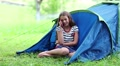 Pretty girl sits on grass near tourist tent and speaks on cell phone HD Footage
