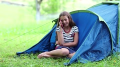Pretty girl sits on grass near tourist tent and speaks on cell phone Stock Footage