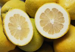 Several whole pomelos and two pomelo halves (close-up) Stock Photos