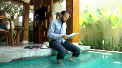 Young businessman with documents sitting by pool in outdoor villa Stock Footage
