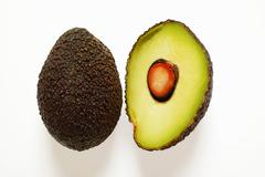 Whole and half mini-avocado Stock Photos