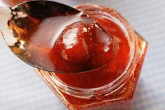 Strawberry jam in jar and on spoon Stock Photos