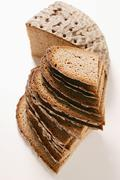 A quarter of a farmhouse loaf and slices of bread in a pile Stock Photos