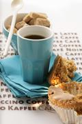 Blue espresso cup, muffin and brown sugar cubes Stock Photos