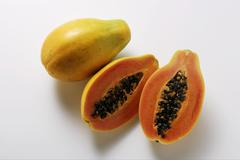 Whole and half papayas Stock Photos