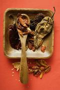 Various dried chili peppers in wooden bowl Stock Photos