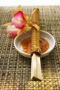 Sweet and sour sauce, flower and chopsticks Stock Photos