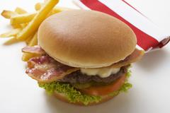 Hamburger with bacon and chips Stock Photos
