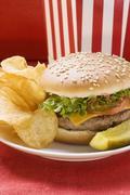 Cheeseburger with potato crisps and gherkin Stock Photos