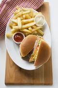 Cheeseburger, chips, mayonnaise, ketchup on plate Stock Photos