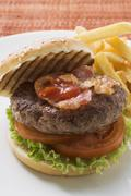 Hamburger with bacon, ketchup and chips Stock Photos