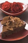 Piece of chocolate cake with chocolate curls, red roses Stock Photos