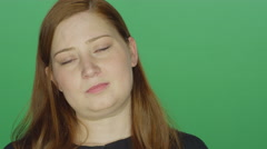 Young redhead woman looking sad, on a green screen background Stock Footage