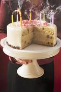 Woman serving birthday cake with blown-out candles Stock Photos