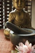 Mortar with pestle in front of Buddha (Asia) Stock Photos