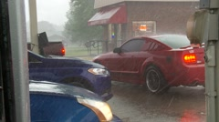 Falling hail and driving rain in severe storm forces cars to seek shelter Stock Footage