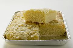 Bee sting cake with flaked almonds in baking tin, partly sliced Stock Photos