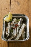Fried anchovies with dried tomatoes in aluminium dish Stock Photos