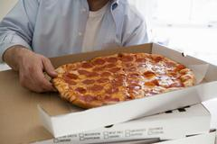 Man holding pizza box containing pepperoni pizza Stock Photos