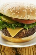 Cheeseburger with tomato and gherkin Stock Photos