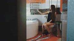 Girl sitting on toilet. Black underwear. Take selfie on monopod. Bathroom. Pose Stock Footage