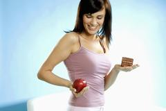 Young woman holding piece of cake and apple in her hand Stock Photos