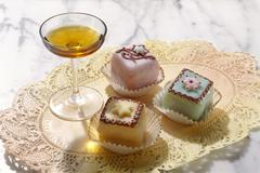 A glass of Amaretto with petit four Stock Photos