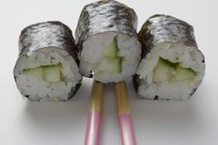 Three maki sushi with cucumber and chopsticks Stock Photos