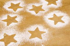 Star shapes outlined in icing sugar on wooden background Stock Photos