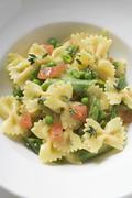 Farfalle with green asparagus, peas and diced tomatoes Stock Photos
