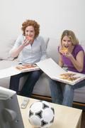 Two friends eating pizza while watching TV Stock Photos