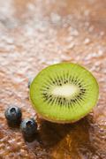 Blueberries and half a kiwi fruit Stock Photos