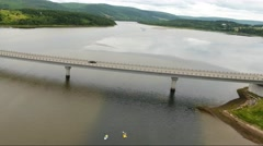 Aerial shot of cars driving over bridge above river Stock Footage