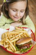 Small girl with hamburger and chips Stock Photos
