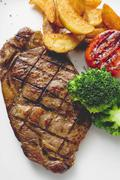 Grilled rump steak with country potatoes and vegetables Stock Photos
