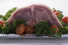 Saddle of suckling pig on silver platter with garnish Stock Photos