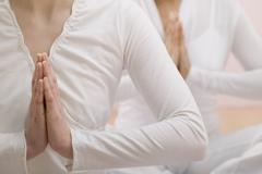 Two young women meditating with hands together Stock Photos