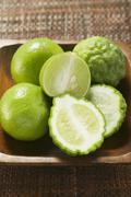 Kaffir limes and limes in wooden bowl Stock Photos