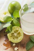 Lime juice in glass, limes and fresh mint Stock Photos