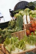 Vegetables and herbs in baskets at a market Stock Photos